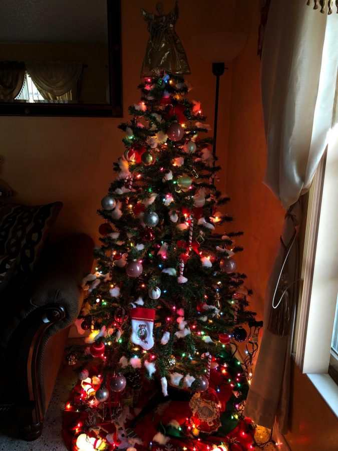 A Christmas tree with a variety of different color ornaments.
