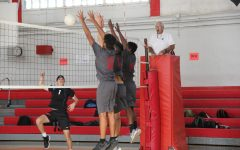 Three Cavaliers leap in the air to defend a volley, aiming to tally a point for their team.