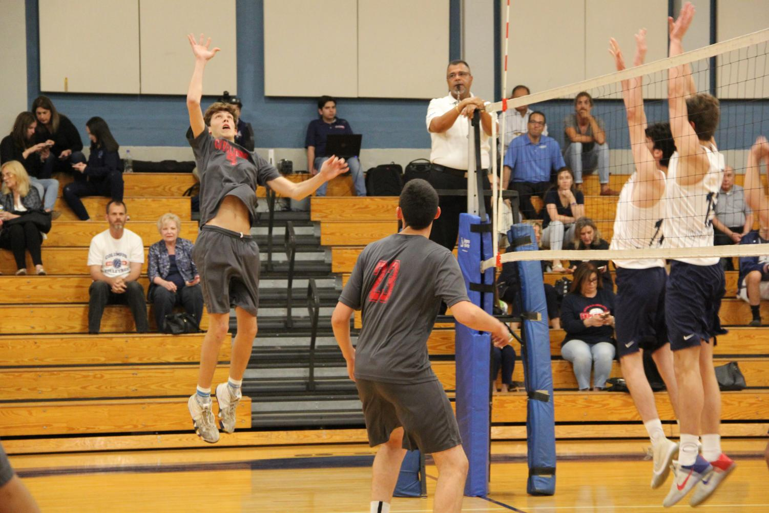 Senior Matthew Wagner leaps in the air, preparing to strike the ball, as two Explorers aim to defend his hit.
