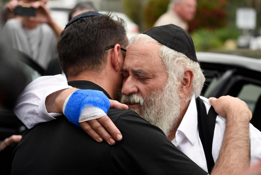 The injured Rabbi embraces another deeply saddened member of his community.