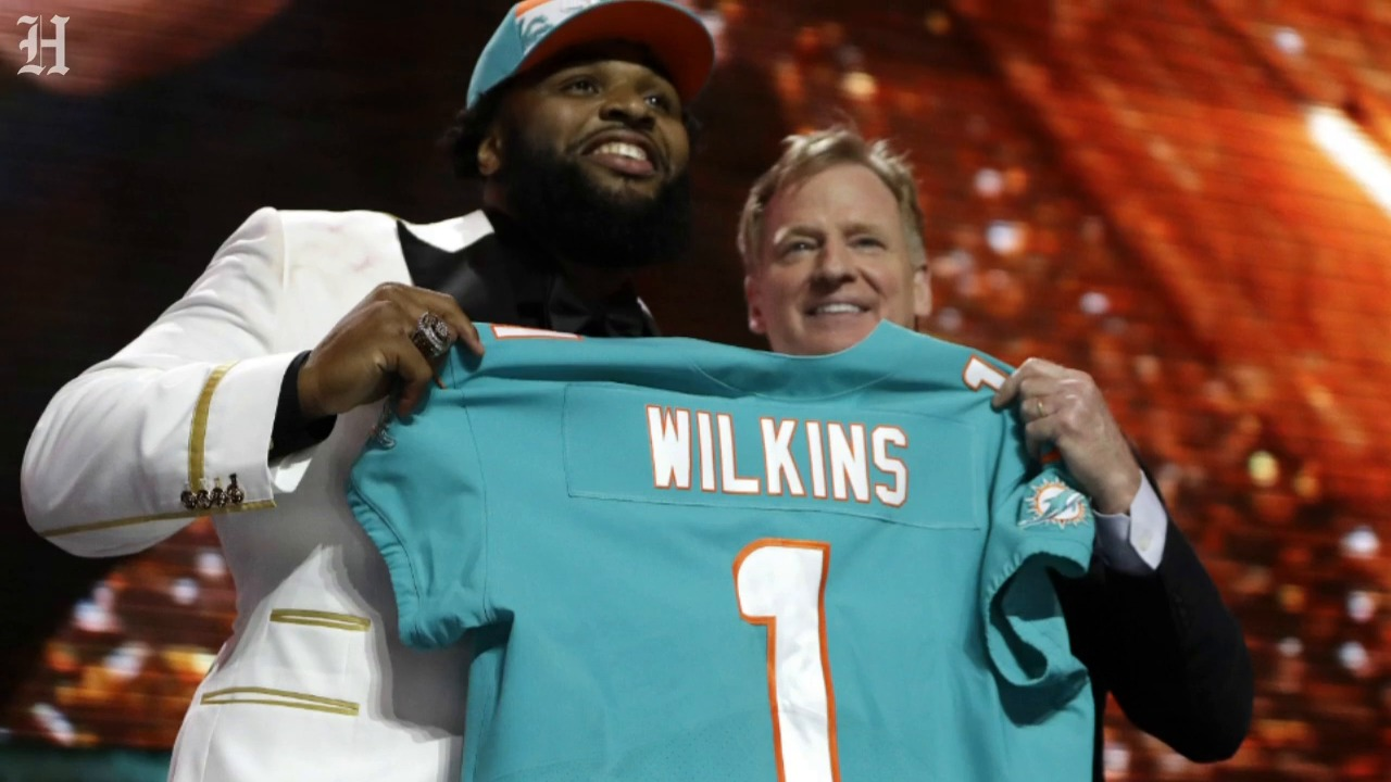 NFL Commissioner Roger Goodell presents the number 13 overall pick, Christian Wilkins, with his Miami Dolphins jersey.