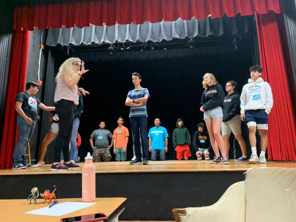 IB Theater teacher Ms. Barrow coaches campers representing Germany on their skit during CavsCamp.