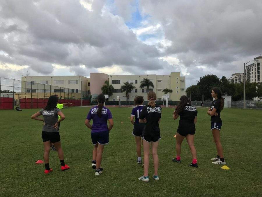 The Miami Tempo soccer team prepares to run a drill on the field at Coral Gables Senior High School.