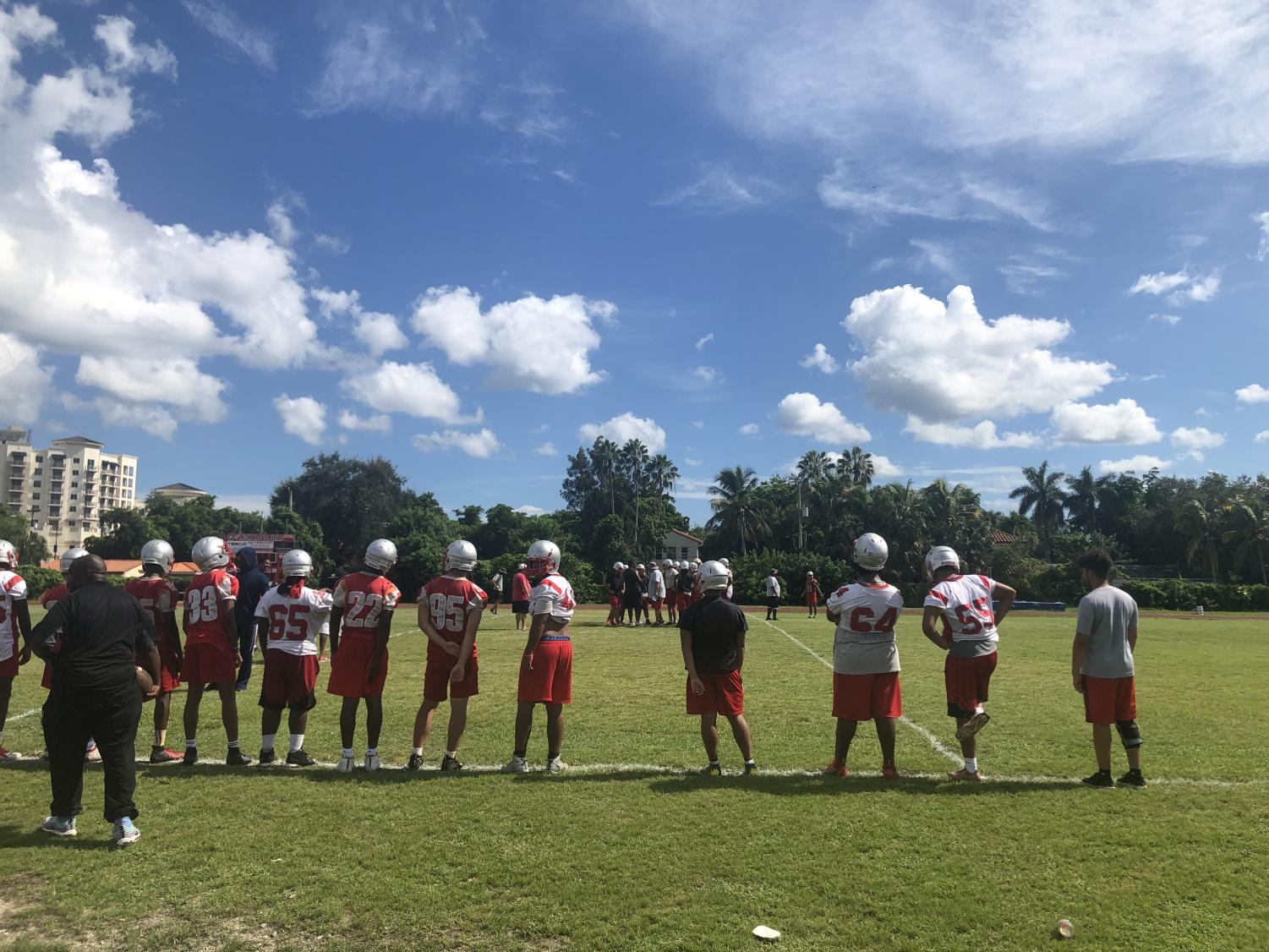 The varsity football team line up on the field, working hard and running their plays during practice.