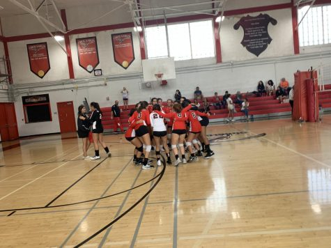 The Lady Cavalier Volleyball team huddles to lift their spirits and discuss their game plan.