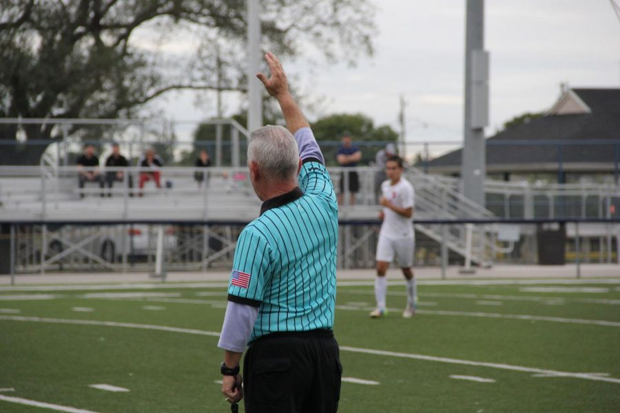 The referee at a Cavalier Soccer game blows his whistle, announcing halftime.