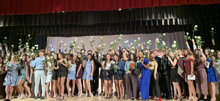 Several proud juniors show off their roses and pins in celebration.
