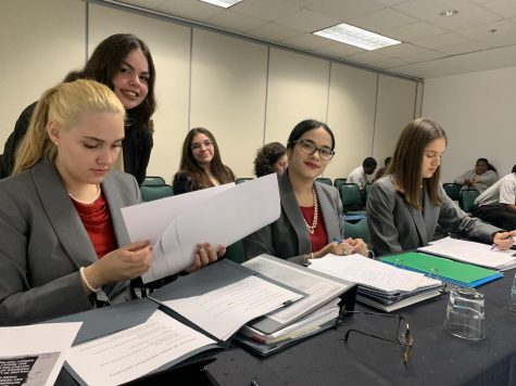Gables' mock trial team prepares its case files and evidence for their presentations as they wait for the trial to start.