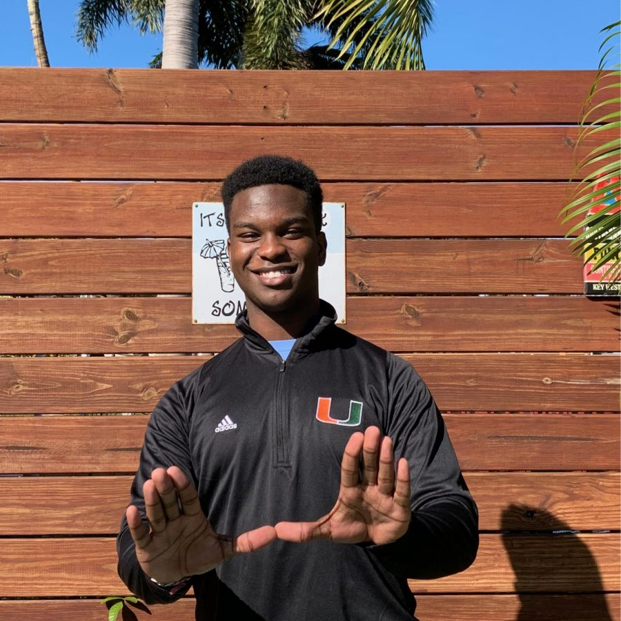 Rodney+Michel+poses+with+his+new+University+of+Miami+gear%2C+adding+in+the+signature+University+of+Miami+%27U%22+hand+symbol.