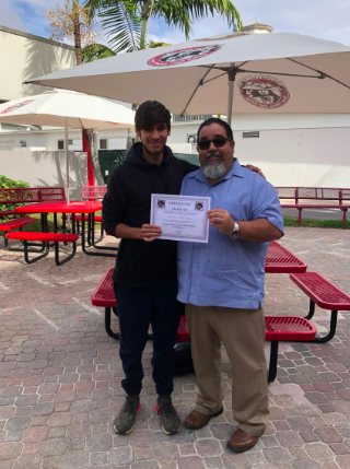 Junior Joseph Serrano posing for a picture with Principal Mr.Costas after receiving the Cavs With Character Award