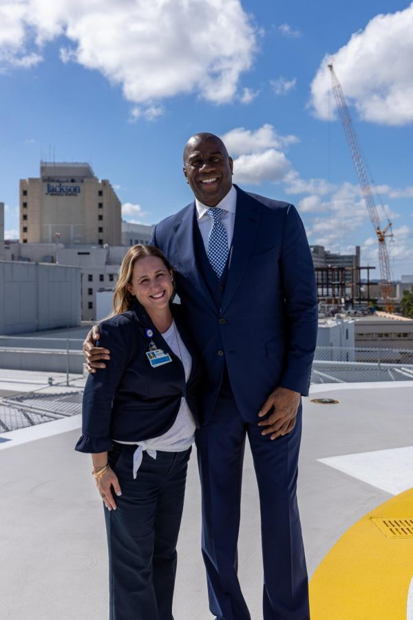 Jennifer Mooney Piedra standing next to Magic Johnson. Piedra is an alumna of Coral Gables Senior High School, and is now at Jackson Hospital working to fight COVID-19.