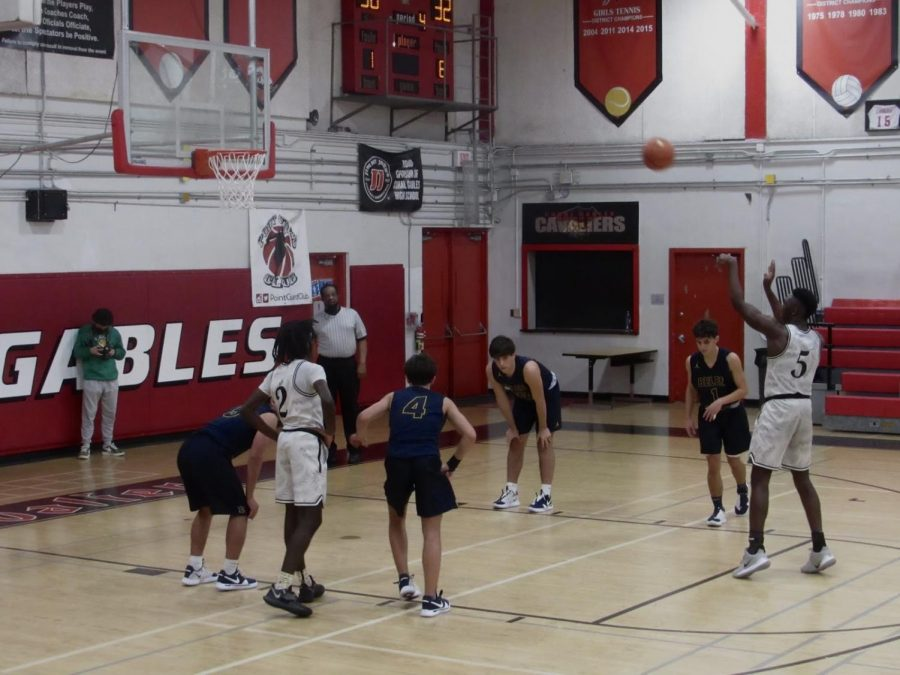 A Gables' player makes a free throw shot as his opponents hesitantly watch.