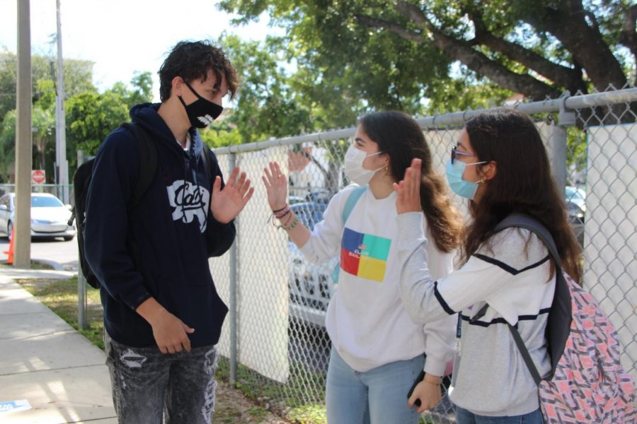 Students chat outside the Gables campus on Oct. 9, wearing masks on their first day back to school.