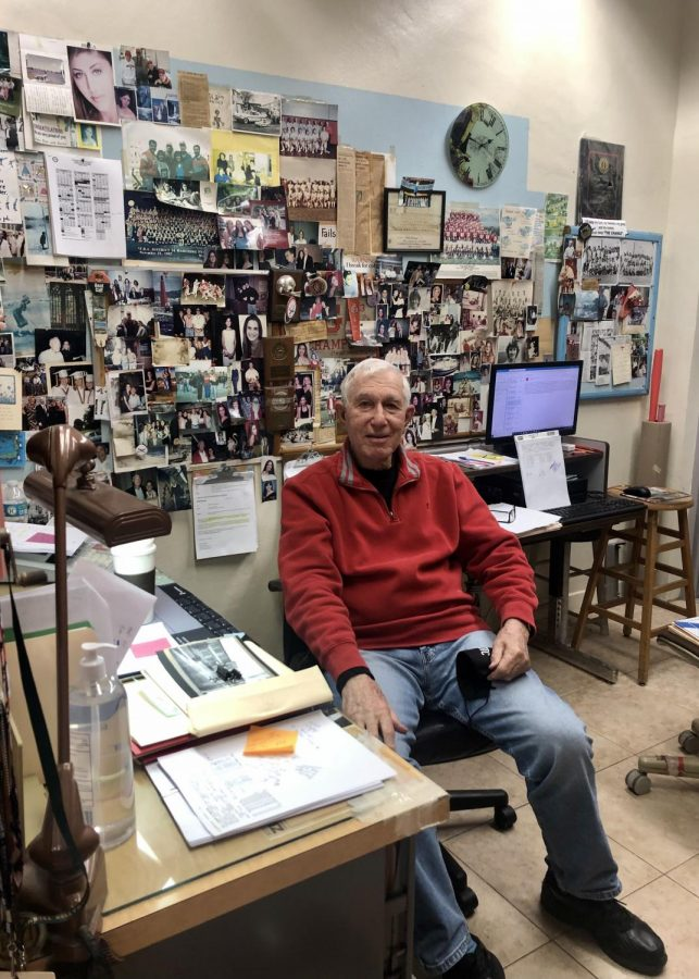 A smiling Mr. Finora sits in his office in front of a wall of old photos he has gathered throughout his time at Gables.