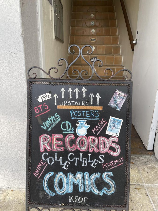 The entrance of the shop is marked by a colorful chalkboard sign.