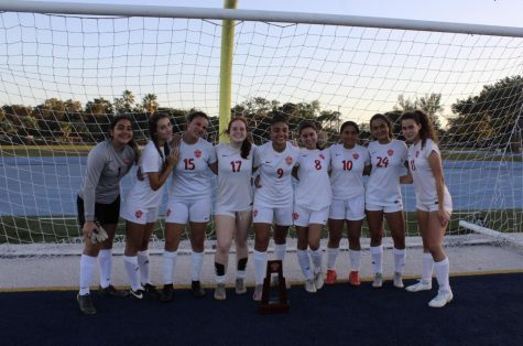 The Lady Cavaliers soccer team celebrates their 4-0 victory over Miami High with their district championship trophy