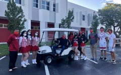 Mr.Grossman sits smiling in the brand-new vehicle as proud Cavaliers surround him and show off their school spirit.