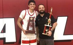 Mr. Govea stands with one of his star players as they hold up the district state champions trophy.