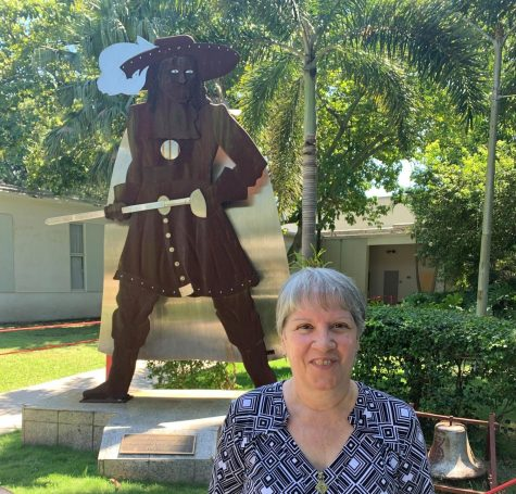 After working at Gables as the IB Secretary for 37 years, Ms. Bello proudly stands next to the Gables Cavalier as she enjoys her final school year.