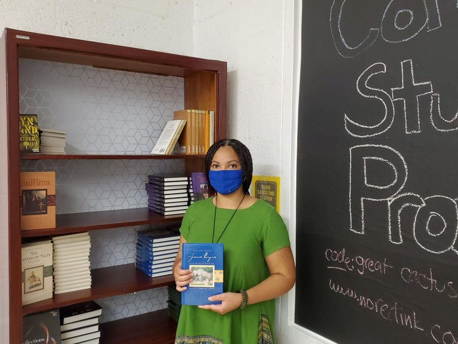 """Ms. LeFebvre pictured by her bookshelf, holding a copy of """"Jane Eyre,"""" her favorite novel."""